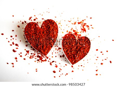 Two hearts filled with grounded red chili flakes - stock photo