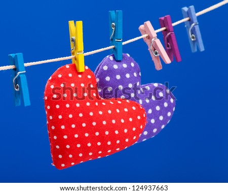 two hearts hanging on a clothesline with clothespins, focus on red. Blue background - stock photo