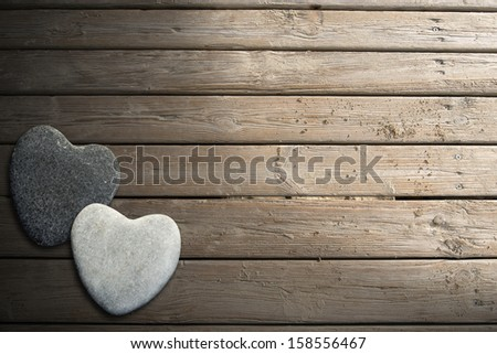 Two hearts of stone on aged beach brown wooden floor over summer sand - stock photo