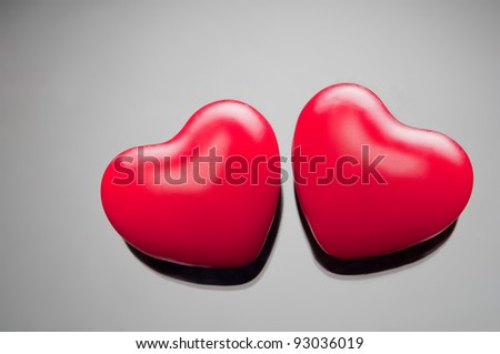two hearts on gray gradient - stock photo