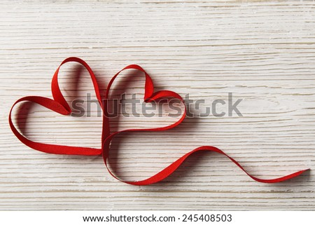 Two Hearts Shape on White Wooden Background. Valentine Day or Wedding Love Concept. Ribbon as Joined Couple - stock photo