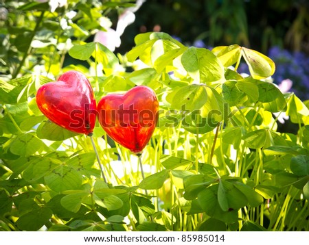 Two hearts surrounded by clover - stock photo
