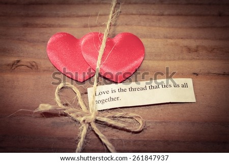 Two hearts tied together with the quote - Love is the thread that ties us all together - stock photo