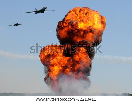 Two heavy bombers attacking ground targets with giant explosions - stock photo