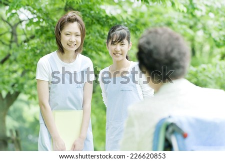 Two helpers greeting senior woman - stock photo