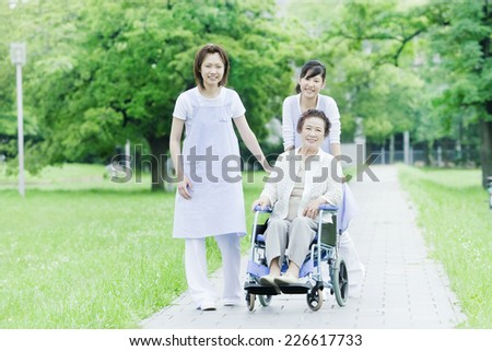 Two helpers walking whilst pushing a wheelchair - stock photo