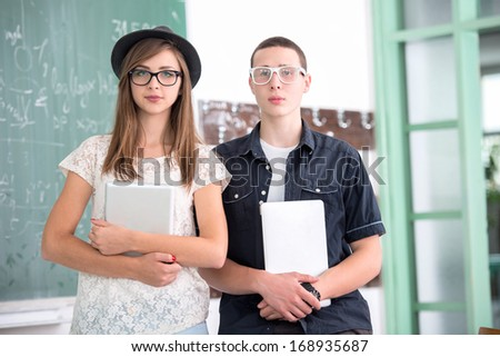 Two highschool students posing with portable computers - stock photo
