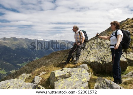 Two hiker resting near mountain summit of Lepples Kofel and being amazed about stunning view of the Alps mountain range and beautiful Defereggen valley in summer, Tyrol, Austria. - stock photo