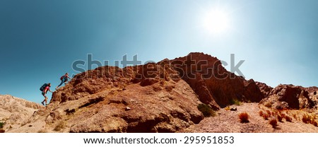 Two hikers climbing the mountain in the desert - stock photo