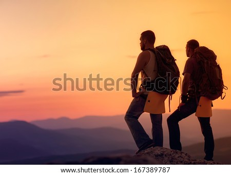Two hikers enjoying sunrise from top of a mountain - stock photo