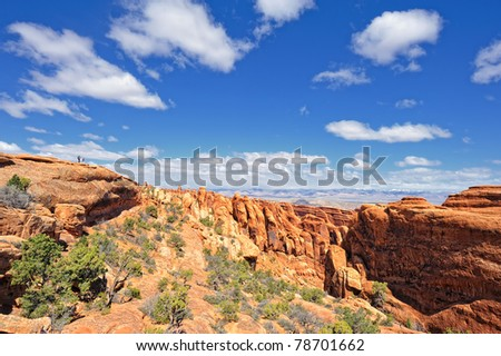 Two Hikers Hiking along the ridge in Arches National Park, Utah, USA - stock photo