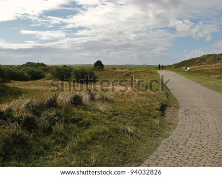 Two hikers on a rural road between grassy hills on Spiekeroog island, Germany - stock photo