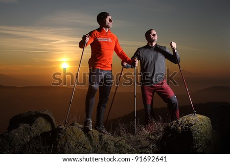 Two hikers on the mountain summit - stock photo