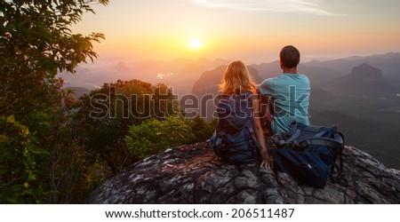 Two hikers relaxing on top of hill and enjoying sunrise over the valley - stock photo