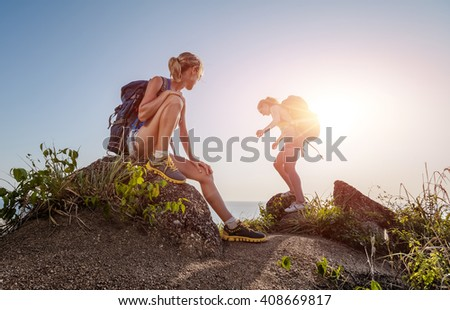 Two hikers standing on top of a hill and enjoying sea view - stock photo