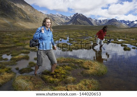 Two hikers wading through pond against mountains - stock photo
