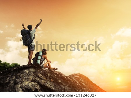 Two hikers with backpacks enjoying sunset view from top of a mountain - stock photo
