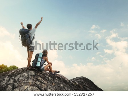 Two hikers with backpacks enjoying view from top of a mountain - stock photo