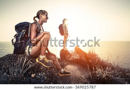 Two hikers with backpacks relaxing on the rock and enjoying tropical sunset - stock photo