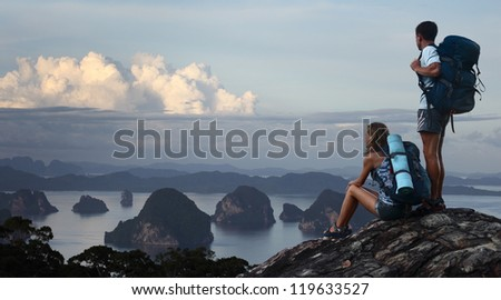 Two hikers with backpacks standing on top of a mountain and enjoying great view to surrounding islands - stock photo