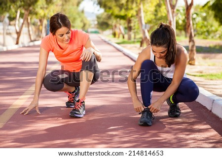 Two Hispanic girls tying their shoes and getting ready for a run outdoors - stock photo