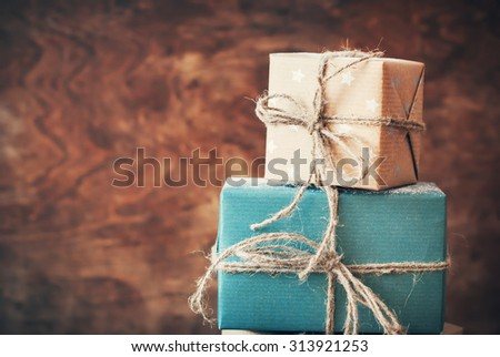 Two Holiday Boxes with Gifts and Natural Twine on Warm Wooden Background. Toned image. Vintage style - stock photo