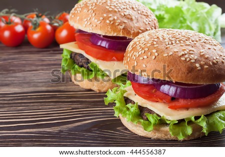 Two homemade cheeseburgers with beef patties and fresh salad on seasame buns, sered on brown wooden table. - stock photo