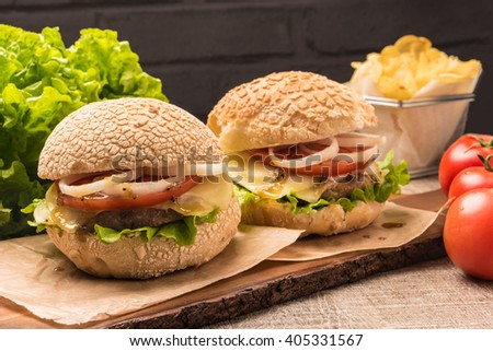 Two homemade vegetarian hamburgers with fresh organic vegetables on rustic wooden background - stock photo