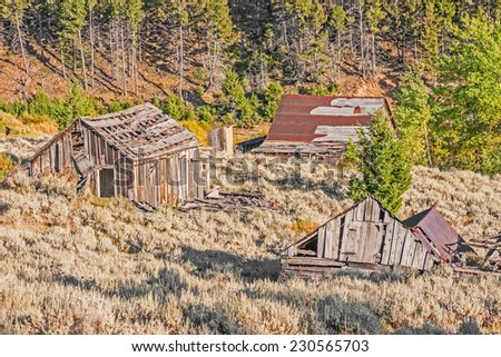 Two homes, an outhouse, and a school were all once part of a thriving mining town in Montana. - stock photo