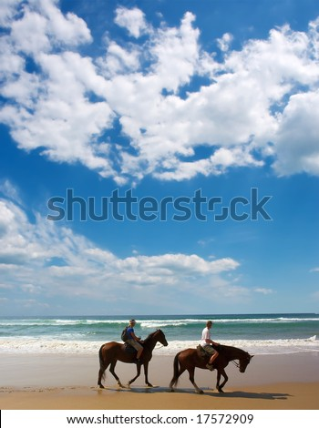 Two horse riders on beach. - stock photo