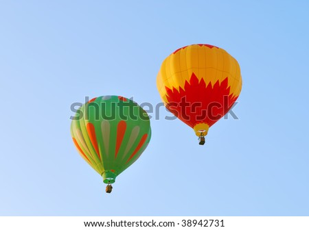 Two hot air balloons against a blue sky - stock photo