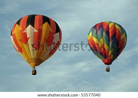 two hot air balloons floating against a cloud streaked blue sky - stock photo