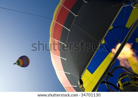 two hot air balloons together in the air, image taken from one balloons basket - stock photo