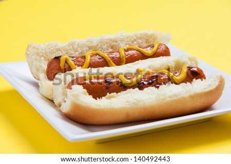 Two hot dogs isolated on yellow background - stock photo