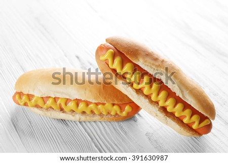 Two hot dogs on wooden background - stock photo