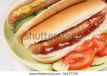 Two hot dogs with ketchup and mustard and salad - stock photo