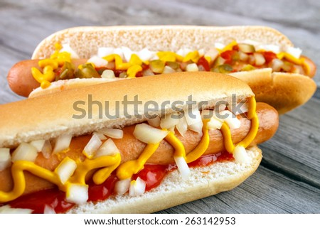 Two hot dogs with ketchup  closeup  , yellow mustard and onion on gray wooden surface - stock photo