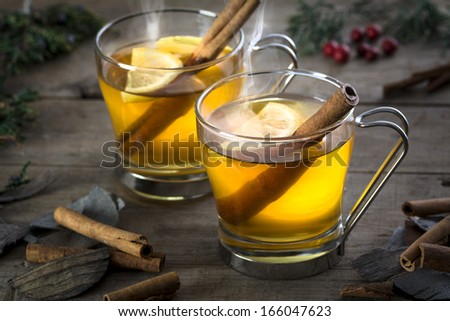 Two hot  whiskey, rum, apple or brandy toddy cocktail drinks with cinnamon set on rustic wood - stock photo