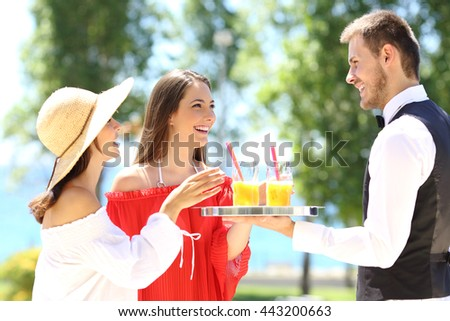 Two hotel customers on summer vacations and a waiter serving them drinks with the ocean in the background - stock photo