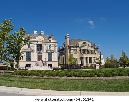 Two huge, new construction homes made to look like historical homes behind a town square that is beautifully landscaped. - stock photo
