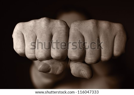 Two human fists as a symbol of aggression. OTHER PHOTOS FROM THIS SERIES IN MY PORTFOLIO. - stock photo