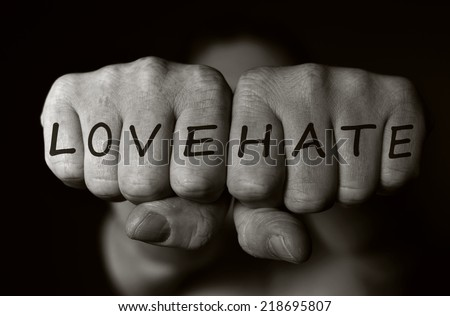 Two human fists as a symbol of love and hate. MANY OTHER PHOTOS FROM THIS SERIES IN MY PORTFOLIO. - stock photo