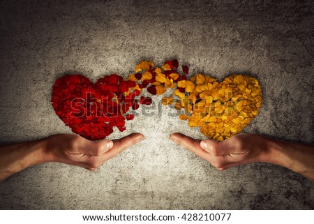 Two human hands holding rose petal hearts on concrete background. Romantic relationship concept. Attachment and love symbol, giving and exchange of feelings and emotions of love. - stock photo