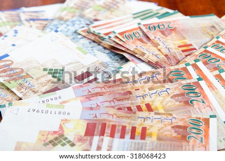 Two hundred and one hundred shekel bank notes against wood background. Concept photo of money, banking ,currency and foreign exchange rates. - stock photo