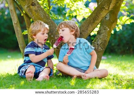 Two hungry little kid boys eating homemade ice cream pops in home's garden, outdoors. Happy blond boys sitting on green grass. healthy food snack for children. - stock photo