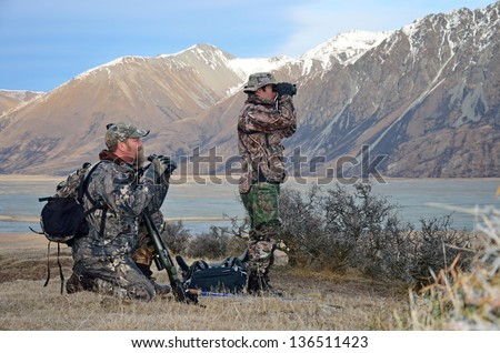 two hunters searching for Himalayan tahr in the Southern Alps of New Zealand - stock photo