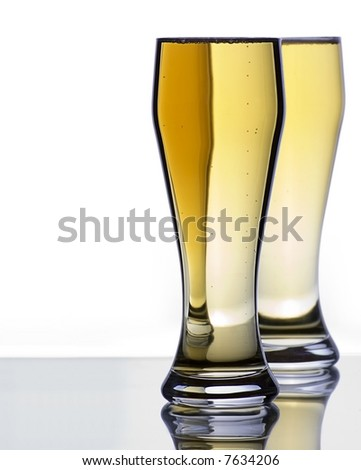 Two Ice Cold Beer Glasses on Reflective Surface with Copy Space - stock photo