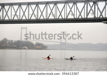 Two in kayaks and two Little Belt Bridges - Denmark - stock photo