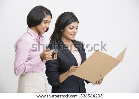 Two Indian Businesswomen Having Informal Meeting on white background. - stock photo