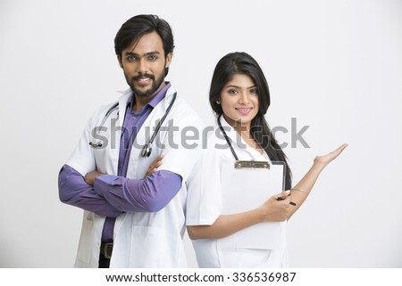 Two Indian young posing attractive doctors on white - stock photo